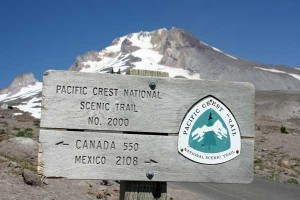 A Pacific Crest Trail sign in front of Mount Hood near Timberline Lodge.